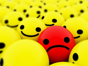 Sad-smiley-between-smiling-smileys